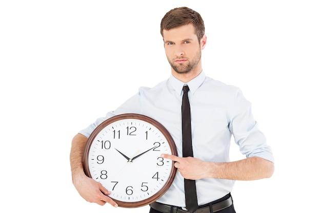時は金なり!彼の手で時計を保持し、白い背景に孤立して立っている間それを指している正装の真面目な若い男