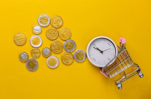 Время - деньги. время для покупок. тележка супермаркета с белыми часами и монетами на желтом