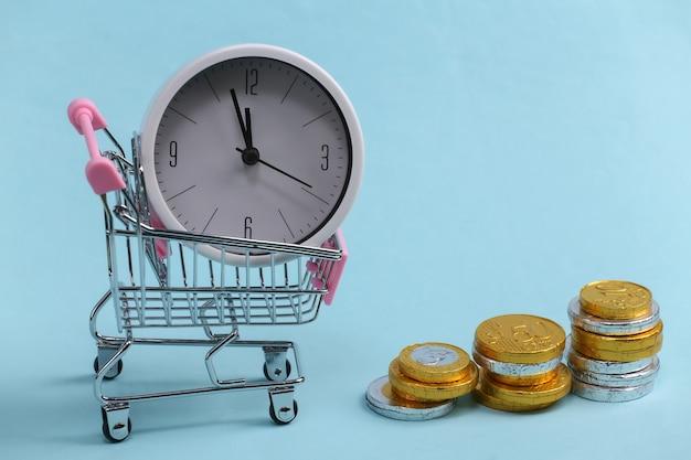 Время - деньги. время для покупок. тележка супермаркета с белыми часами и стопкой монет на синем