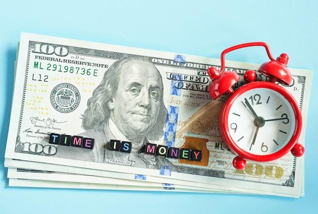 Время деньги текст и красный будильник на фоне американских сотен долларовых купюр, крупным планом. креативная концепция цитата дня.