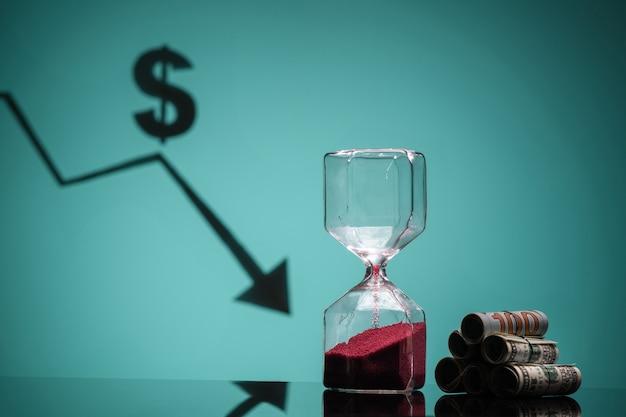 Время - деньги. скрученные долларовые купюры и крупный план песочных часов. стрелка падающих цен