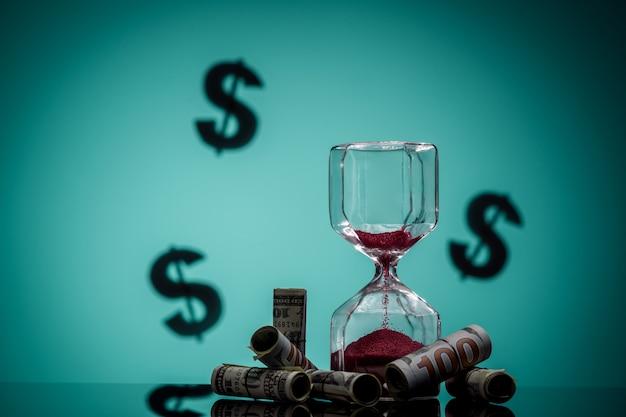 Время - деньги. скрученные долларовые купюры и крупный план песочных часов.