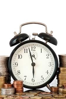 Концепция time is money: будильник и много монет евро