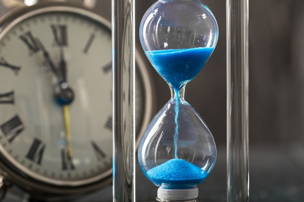 Time is passing blue hourglass close up
