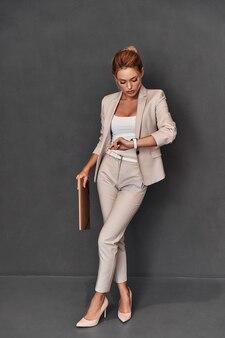 時間がなくなっています。灰色の背景に立っている間時間をチェックするスマートカジュアルな服装で自信を持って若い女性の完全な長さ
