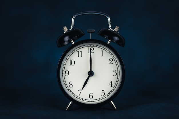 The time is seven o'clock in the morning. time - 07-00. retro clock. dark background. lifting concept for work. copy space and cut out.