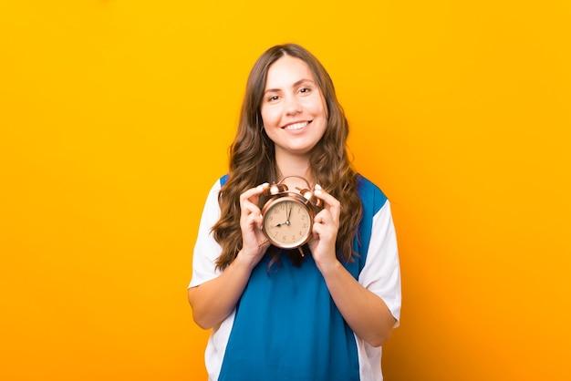 시간은 가장 소중한 자원입니다. 알람 시계를 들고 있는 여성의 초상화.
