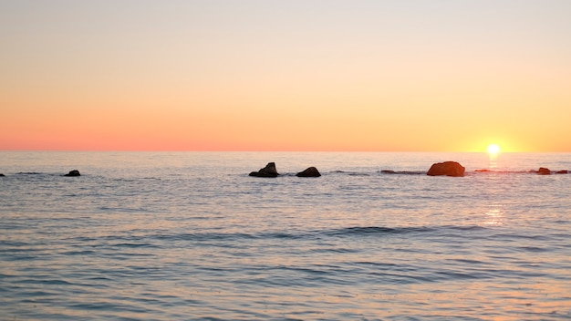 日の出のタイムラップ。海の上の澄んだ空の日の出の間にオレンジ色の黄金色の赤い空