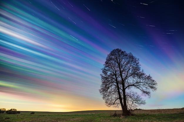 緑の野原に星とタイムラプス夕焼け空