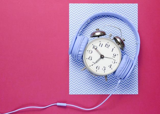 시간은 복고풍 알람 시계와 헤드폰으로 음악 개념을 듣습니다.