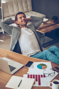 Time for little rest. top view of cheerful young handsome man keeping hands behind his head and eyes closed with smile while sitting at his working place