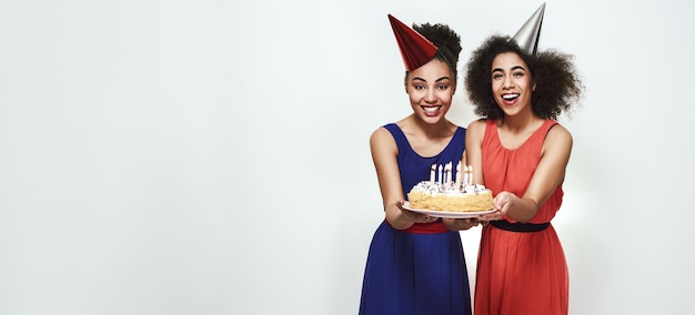 Time to make a wish wide photo of happy young afro american women in party