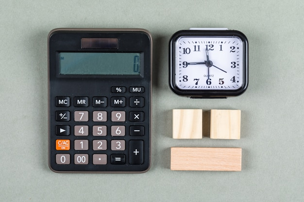 돋보기, 나무 블록, 계산기와 회색 배경 평면도에 시계 시간 관리 및 회계 개념. 가로 이미지