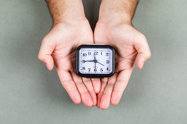 회색 배경 평면도에 시계와 시간 관리 및 시계 똑 딱 개념. 손에 시계를 들고입니다. 가로 이미지