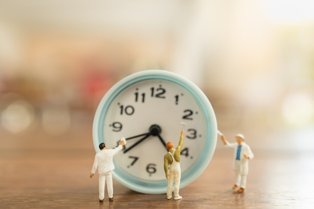 Time management concept. close up of group of worker miniature people figures clean and paint vintage round clock on wooden table.
