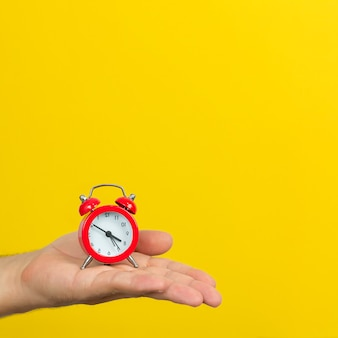 Time management concept. hand with small red alarm clock on trendy yellow color background