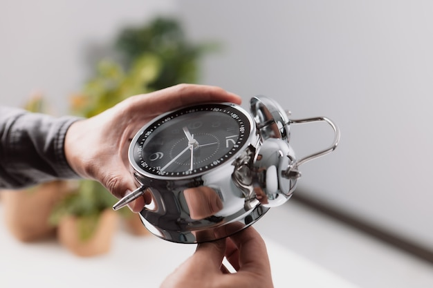 Time management concept. male hand adjusting or changing the time on clock.