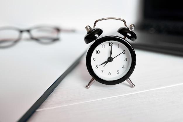 時間管理の概念、オフィスの職場、ノートブック、コンピューター、ラップトップ、白い木製のオフィスの机の上の黒い目覚まし時計、コピースペース。