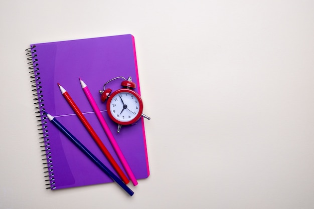 時間管理の概念。赤いビンテージの目覚まし時計、鉛筆、紫のメモ帳