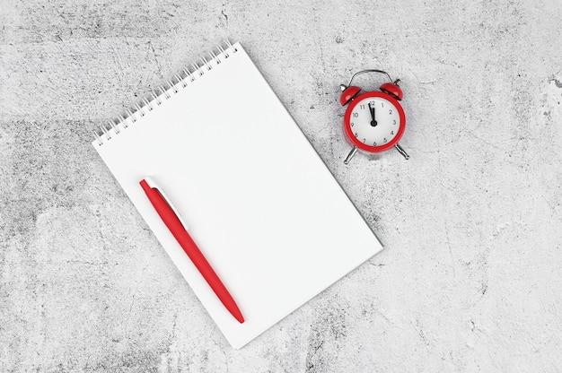 時間管理の概念。やることリスト:赤い目覚まし時計、鉛筆、ノート