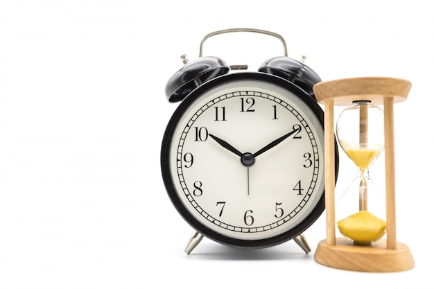 Time management concept. vintage round alarm clock with sandglass on white surface