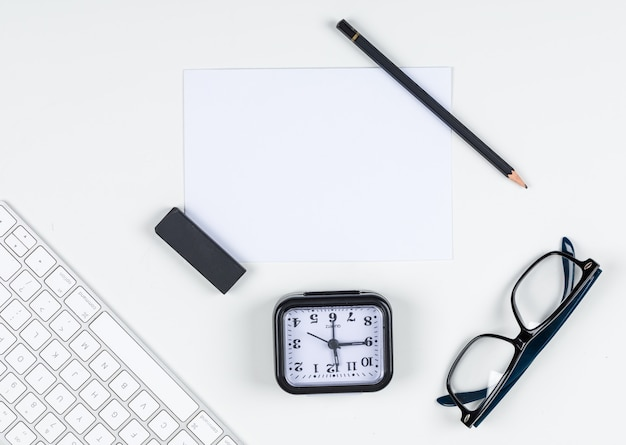 Time management concept with clock, pencil, eraser, eyeglasses, paper, keyboard on white background space for text, top view. horizontal image