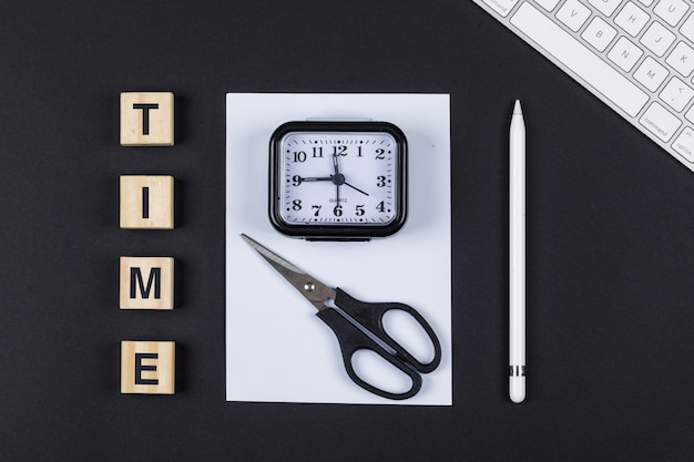 Time management concept with wooden blocks, scissors, clock, pencil, paper, keyboard on black background top view. horizontal image