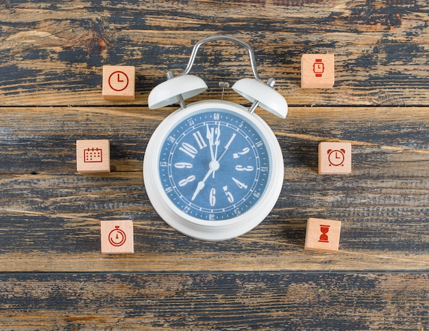Time management concept with wooden blocks with icons, big clock on wooden table flat lay.