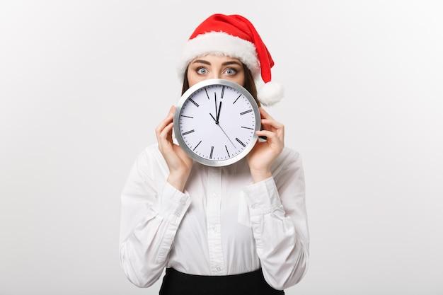 時間管理の概念-白い壁に隔離された時計の後ろに隠れているサンタの帽子を持つ若いビジネス女性。