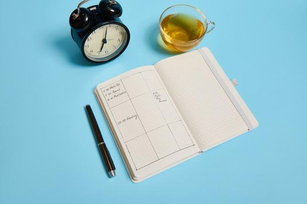 시간 관리, 마감 시간 및 일정 개념:일정 계획에 대한 알람 시계, 계획이 있는 주최자, 잉크 펜 및 텍스트를 위한 공간이 있는 파란색 배경에 차가 있는 투명한 유리 컵. 플랫 레이.