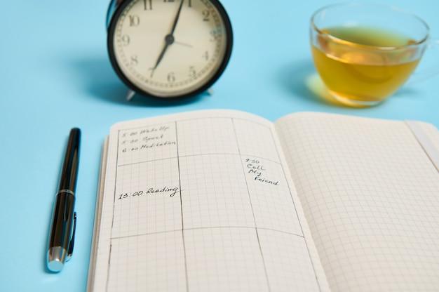 시간 관리, 마감 및 일정 개념:일정 계획에 대한 알람 시계, 계획이 있는 주최자, 잉크 펜 및 텍스트를 위한 공간이 있는 파란색 배경에 차가 포함된 투명한 유리 컵