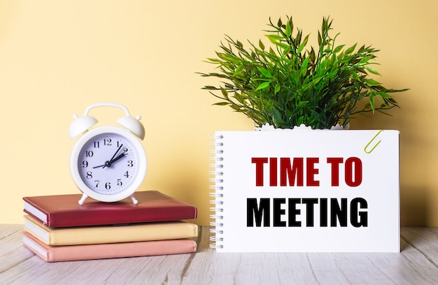 Time to meeting is written in a notebook next to a green plant and a white alarm clock, which stands on colorful diaries.