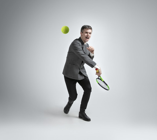 Time for movement. man in office clothes plays tennis isolated on grey background
