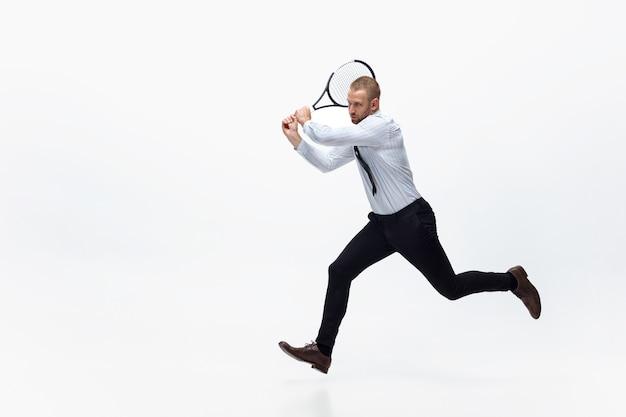 Tempo per il movimento. l'uomo in vestiti dell'ufficio gioca a tennis isolato su bianco.