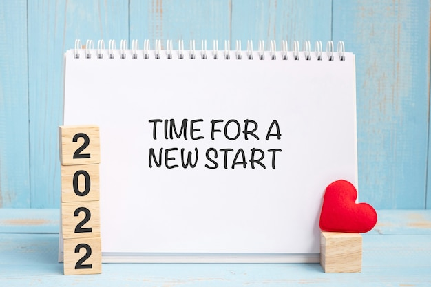 Time for a new start words and 2022 cubes with red heart shape decoration on blue wooden table background. new year newyou, goal, resolution, health, love and happy valentine's day concept
