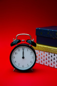Time for new year and christmas gifts a black vintage alarm clock and gift boxes  on a red
