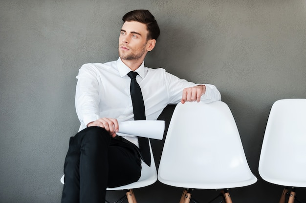 待つ時間。灰色の背景に対して椅子に座っている間紙を保持している思いやりのある若い男