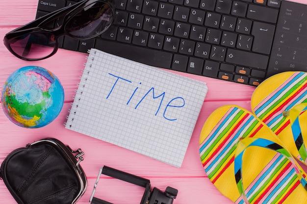 ピンクのテーブルトップの背景に女性の旅行者アクセサリーメガネ財布とビーチサンダルでノートブックの時間。グローブと黒のキーボード。
