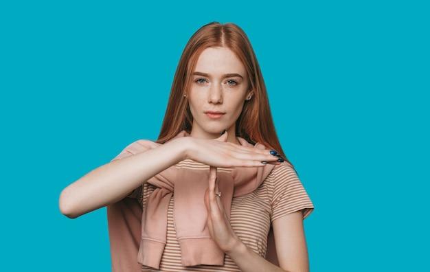 タイムアウト !そばかすのある美しい若い赤い髪の女性は、青い背景に対して真剣にカメラを見て手でタイムアウトを示しています。