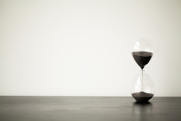 Time passing. a side view of an hourglass with falling sand