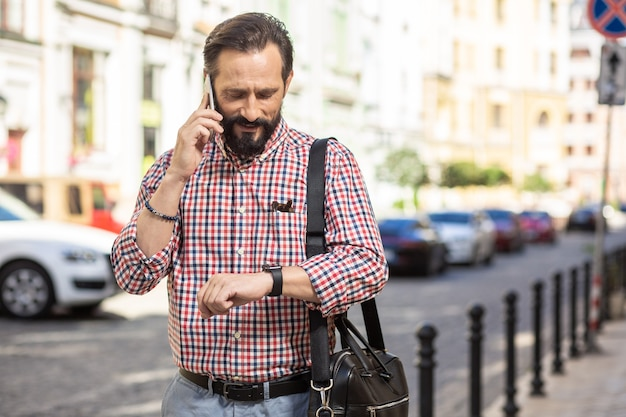 時間的制約。屋外で時間をチェックしながら電話で話している楽しいハンサムな男