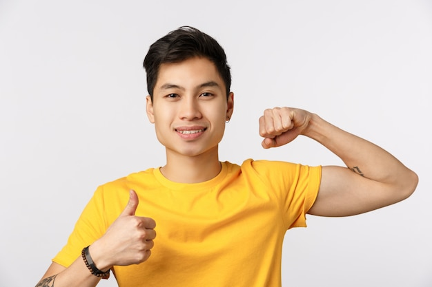 Time pump it up. attractive young asian man in yellow t-shirt showing muscle and thumb-up, smiling, encourage do physical exercises, come gym together, want gain strong biceps