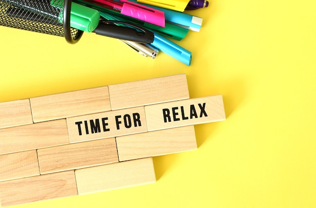 Time for relax text on a wooden block wooden blocks stacked next to pens and pencils on a yellow bac...
