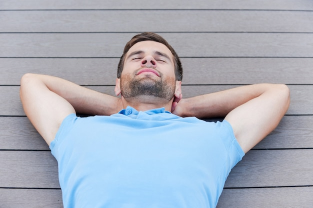 Time to relax. top view of handsome young man keeping eyes closed and smiling while lying down on the hardwood floor