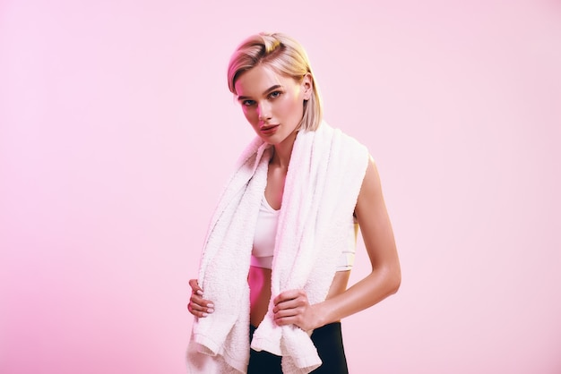 Time for rest attractive young blonde woman with towel on shoulders looking at camera while