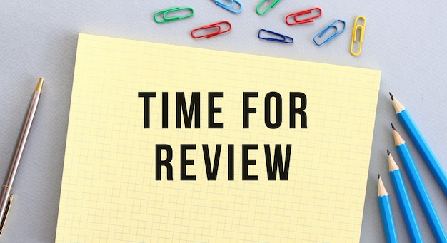 Time to review text in notebook on gray background next to pencils pen and paper clips