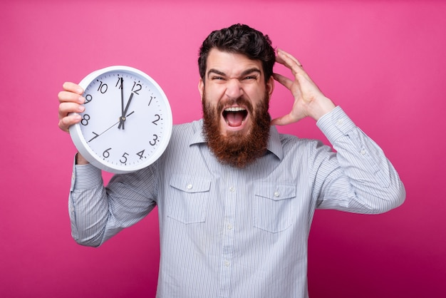 Time runs! i'm late. young bearded man is stressed, holding a white clock and an hand on his head, screaming mad.