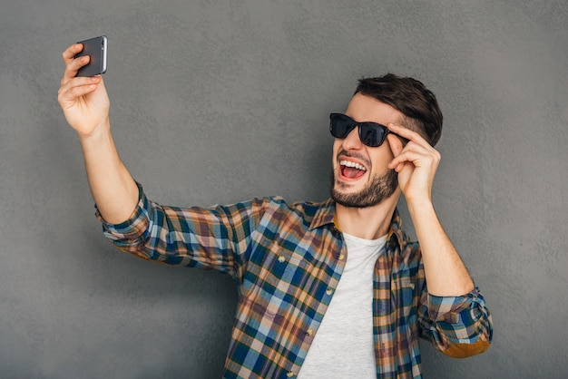 Time for selfie. cheerful young man in sunglasses making selfie while standing against grey background