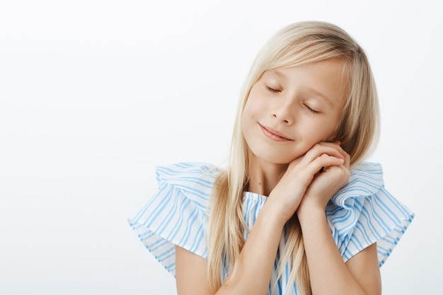 Time to sleep. sleepy cute little european girl with blond hair, closing eyes and leaning on palms as if sleeping, feeling pleased and tired after spending awesome time with friends over gray wall