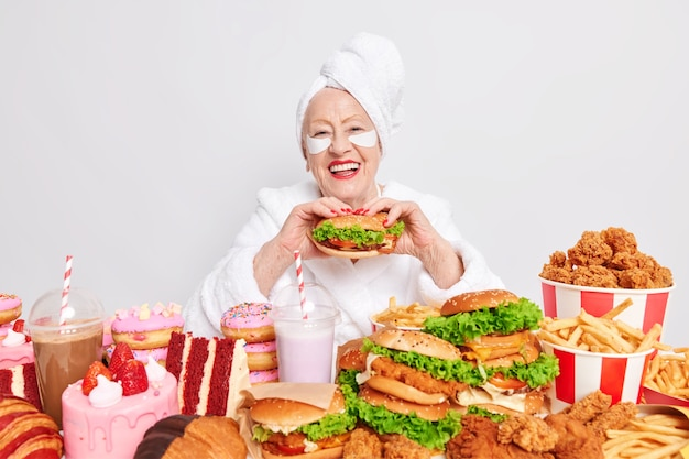 Time for snack. happy old lady eats appetizing hamburger smiles and eats high calorie food.